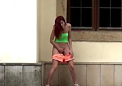 Slutty red haired girl in mini skirt pees on the backwards of house