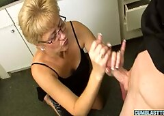 Mature blonde wanks cock while on her knees